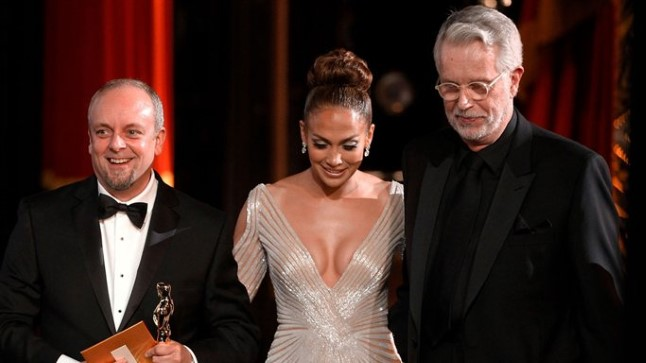 """Jennifer Lopez lahkumas Oscarite gala lavalt koos parima grimmi auhinna võitnud Mark Coulier' (vasakul) ja J. Roy Hellandiga (""""Raudne leedi"""")."""