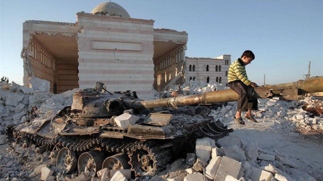 SÕJAAJA  MÄNGUASI: Poiss mängib Süüria valitsusvägede tabamuse saanud tankil lahingutes putustatud mošee ees Aleppost põhja pool.