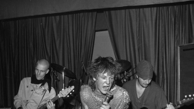 JÕULINE PUNKROKKAR: 19aastane Ivo Uukkivi, punkarinimega Munk, 23.oktoobril 1984 Tallinna 49.keskkoolis koos kaks aastat tegutsenud Velikije Lukiga lavadebüüti tegemas. Vasakul mängib kitarri Villu Tamme ja paremal bassi Raivo Pilt. Ehkki esimesed 20 minutit kulus pillide häälestamisele, oli publiku vastuvõtt tormiline.