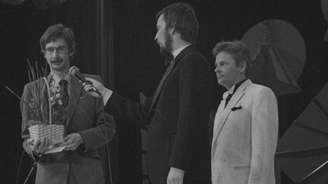 AUTASUSTAMINE: Andres Valkonen (lillekorviga) 1984. aasta Arne Oidi lauluvõistlusel võtmas vastu peaauhinda laulu «Uusaastaöö» eest, mida esitas Ivo Linna (paremal). Laval ka konferansjee Vello Orumets (mikrofoniga) ning ETV ja ER estraadiorkestreid juhatanud Peeter Saul (vasakul).
