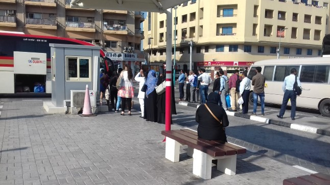 Meeste ja naiste järjekord minnes Abu Dhabi bussile