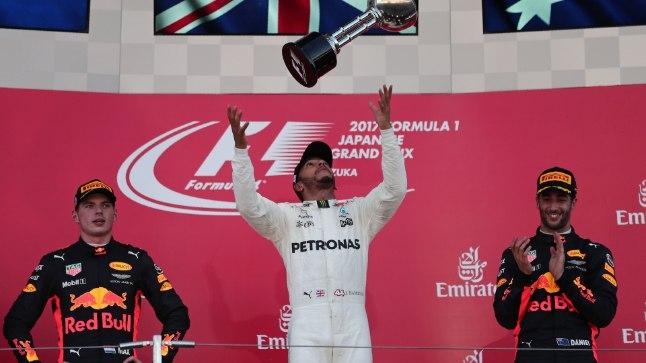 Lewis Hamilton (keskel) hüpitamas Jaapani GP võidukarikat.