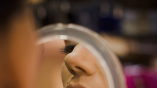 PantherMedia 3507121 Close up portrait of young woman looking in handheld mirror
