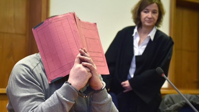Niels Hoegel varjab kohtus nägu. Foto on tehtud veebruaris 2015. Taamal mehe advokaat.