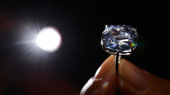 TO GO WITH AFP STORY  (FILES) A model holds a 12.03-carat blue diamond during a press preview by auction house Sotheby's in Geneva on November 4, 2015. A 12.03-carat blue diamond could fetch a record $55 million (47 million Euros) when it goes under the hammer by Sotheby's on November 11 in Geneva. Categorised as a fancy vivid blue diamond, the Blue Moon, discovered in South Africa in January last year, is the largest cushion-shaped stone in that category to ever appear at auction.  AFP PHOTO / FABRICE COFFRINI