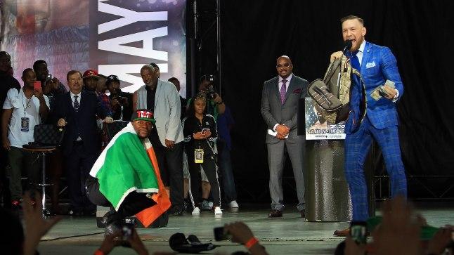 VEIDER SPORDIPIDU. Floyd Mayweather Jr. kükitab Iirimaa lipp õlgadel, samal ajal irvitab Conor McGregor vastase seljakotist leitud 5000 dollari üle.