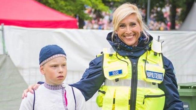 Fotol aitab politseinik ühte laulupeol eksinud last.