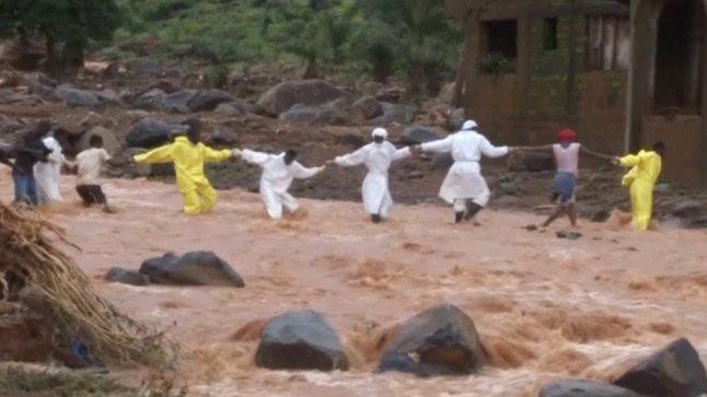 Päästjad ja vabatahtlikud hoiavad kätest kinni, et mudajõge ületada