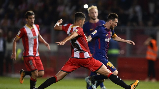 Girona's defender Juanpe Ramirez (C) vies with Barcelona's forward from Argentina Lionel Messi during the Spanish league football match Girona FC vs FC Barcelona at the Montilivi stadium in Girona on September 23, 2017. / AFP PHOTO / Josep LAGO
