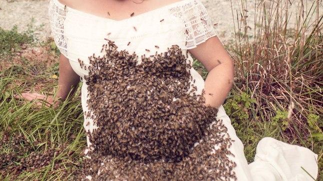 Rase naine poseeris koos mesilastega.