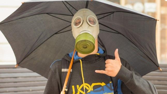 Gaasimask mees ja vihmavari Tartus Rüütli tänaval