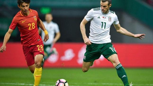 Wang Shenchao (vasakul) takistamas Walesi staari Gareth Bale'i.