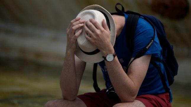 PALAVUS TEEB LIIGA: mees kaitsmas end suvepäeval Lõuna-Hispaanias Sevillas kuumuse eest.