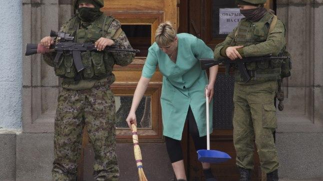 ROHELISED MEHIKESED: Kaks eraldusmärkideta relvastatud sõdurit valvavad Krimmi pealinnas Simferopolis valitsushoone ust, kohalik naine pühib kokku purunenud klaasi. On 12. märts 2014, linna suunas marsib sadade Vene sõdurite konvoi, päev varem võtsid Vene võimud poolsaare ühegi lasuta üle.