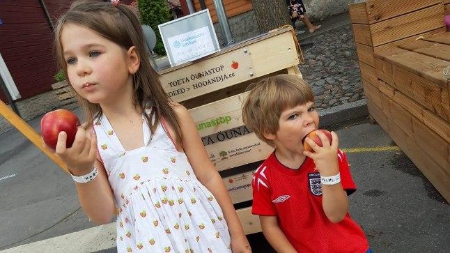 Marika Juusu lapsed Karmela ja Mattias rõõmustamas Paide keskväljakul avatud esimese Õunastopi üle.