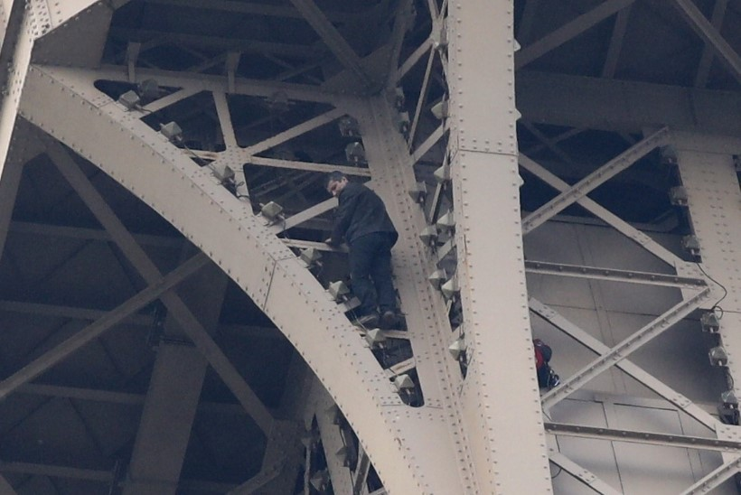 FOTOUUDIS   Mees üritab mööda Eiffeli torni üles ronida