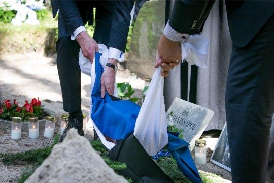 GALERII   Luuletaja Henrik Visnapuu tuhaurn sängitati sinimustvalge lipu sees Metsakalmistule
